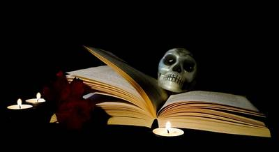 Antichrist signs: Open old book with a skull