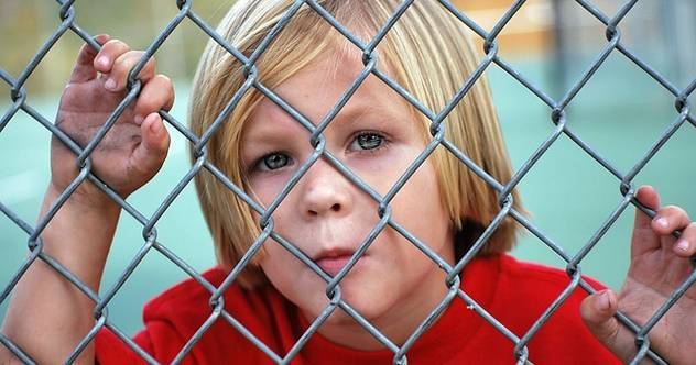 Child: Boy behind metal link fence