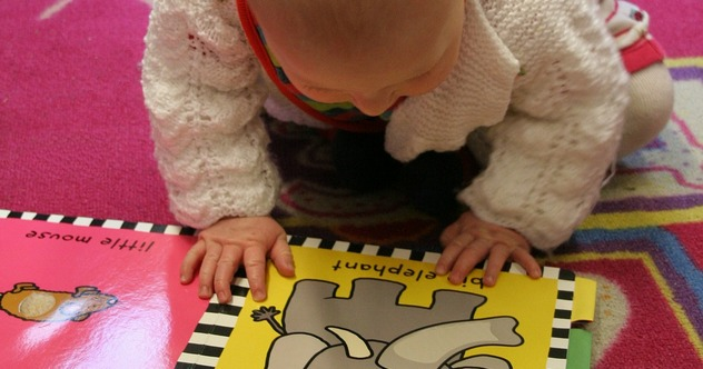 Baby looking at a learning book