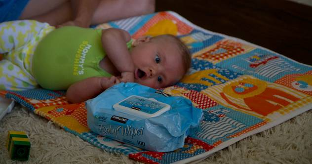 Baby looking at baby wipes